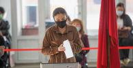 Девушка голосует на избирательном участке в здании КРСУ в ходе голосования на выборах седьмого созыва ЖК