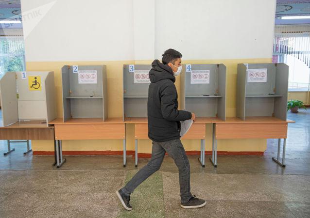 Парень голосует на избирательном участке в здании КРСУ в ходе голосования на выборах седьмого созыва ЖК