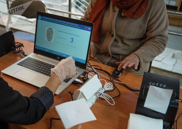 Женщина голосует на избирательном участке в здании КРСУ в ходе голосования на выборах седьмого созыва ЖК