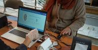 Женщина проходит биометрическую идентификацию на выборах седьмого созыва ЖК