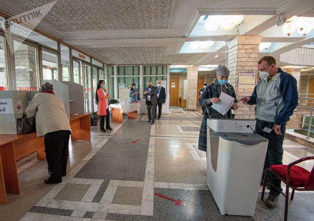 Люди на избирательном участке в здании КРСУ в ходе голосования на выборах седьмого созыва ЖК