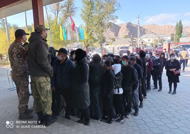 Люди стоят в очереди на одном из избирательных участков в городе Нарын в ходе голосования на выборах седьмого созыва ЖК