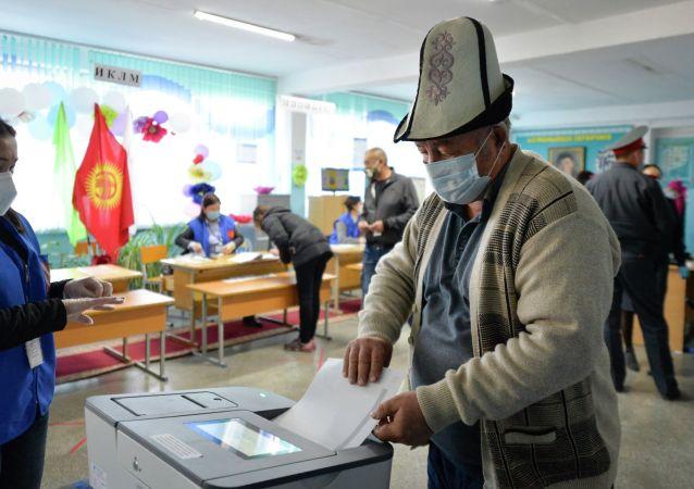Мужчина в маске для защиты от коронавируса опускает бюллетень во время парламентских выборов в селе Беш-Кунгей в 15 км (9 милях) к югу от Бишкека. 4 октября 2020 года