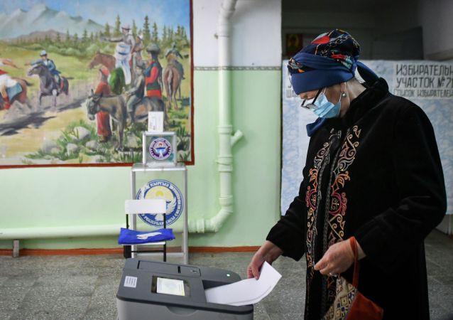 Женщина в маске для защиты от коронавируса опускает бюллетень во время парламентских выборов в селе Беш-Кунгей. 4 октября 2020 года
