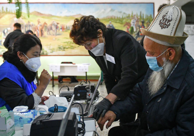 Избиратель в маске проходит процедуру идентификации для голосования во время парламентских выборов в селе Горная Маевка. 4 октября 2020 года