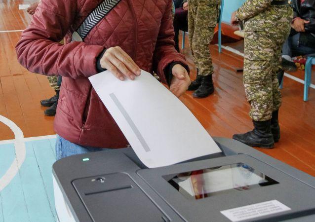 Женщина опускает бюллетень во время парламентских выборов в селе Беш-Кунгей. Чуйская область, 4 октября 2020 года