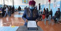 Женщина в маске опускает свой бюллетень на избирательном участке во время парламентских выборов в Кыргызстане в селе Беш-Кунгей. Архивное фото