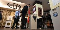 Мужчина опускает бюллетень в урну для голосования на избирательном участке № 9005 в посольстве КР в Москве