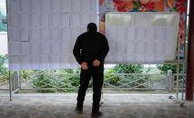 Избиратель ищет себя в списке на участке во время выборов. Архивное фото