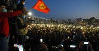 Митингующие с включенными вспышками на телефонах во время митинга на площади Ала-Тоо в Бишкеке
