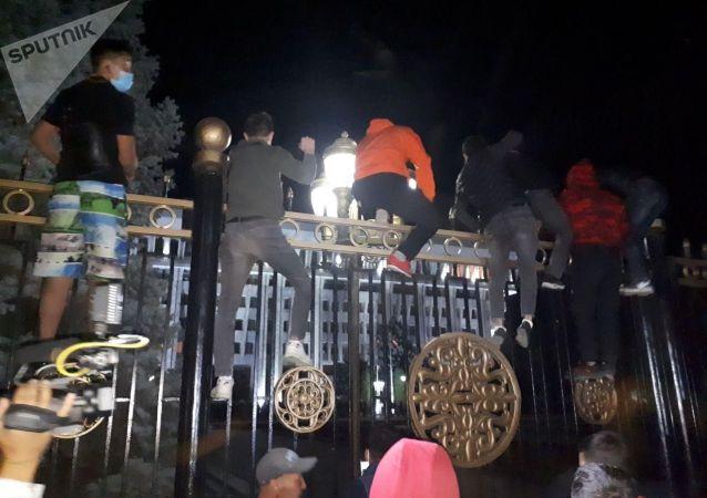 Протестующие забрались на забор здания парламента на площади Ала-Тоо в Бишкеке во время митинга против результатов выборов в Жогорку Кенеш