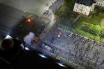 На видео можно увидеть столкновения между сотрудниками милиции и митингующими, как горят машины и взрываются светошумовые гранаты.