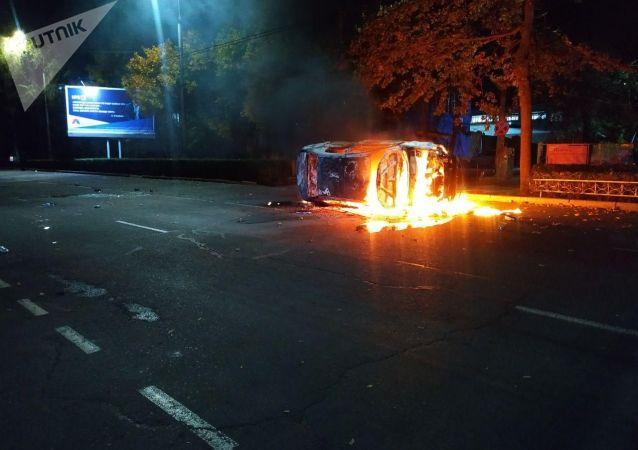 Горящая патрульная машина во время беспорядков в Бишкеке, из-за недовольств над результатами выборов в Жогорку Кенеш