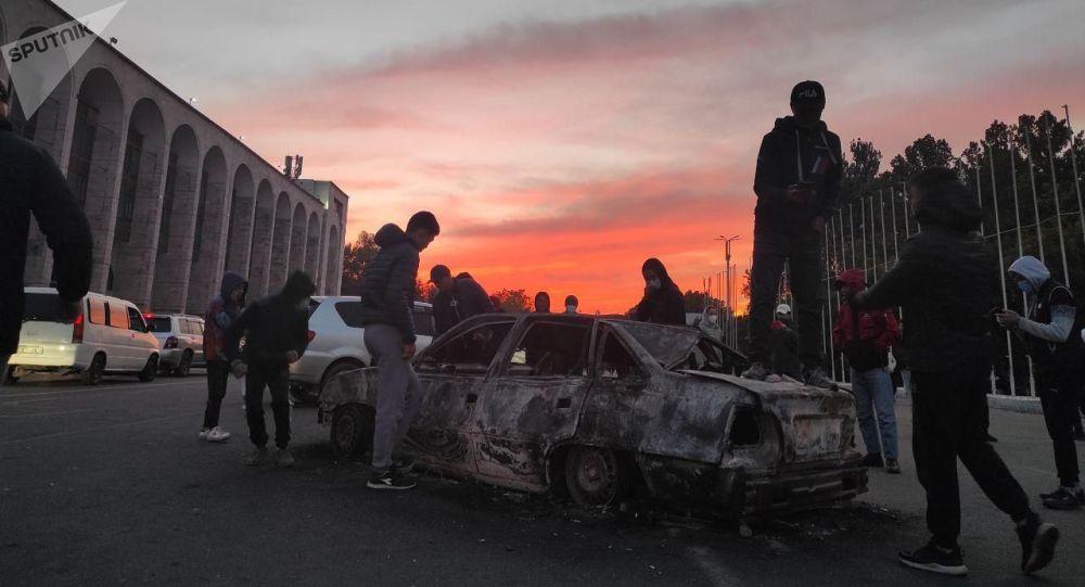 Молодые люди на площади Ала-Тоо в Бишкеке, через сутки после штурма здания Белого дома после парламентских выборов
