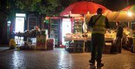 Дружинник на фоне ларьков в ночное время в городе Бишкек