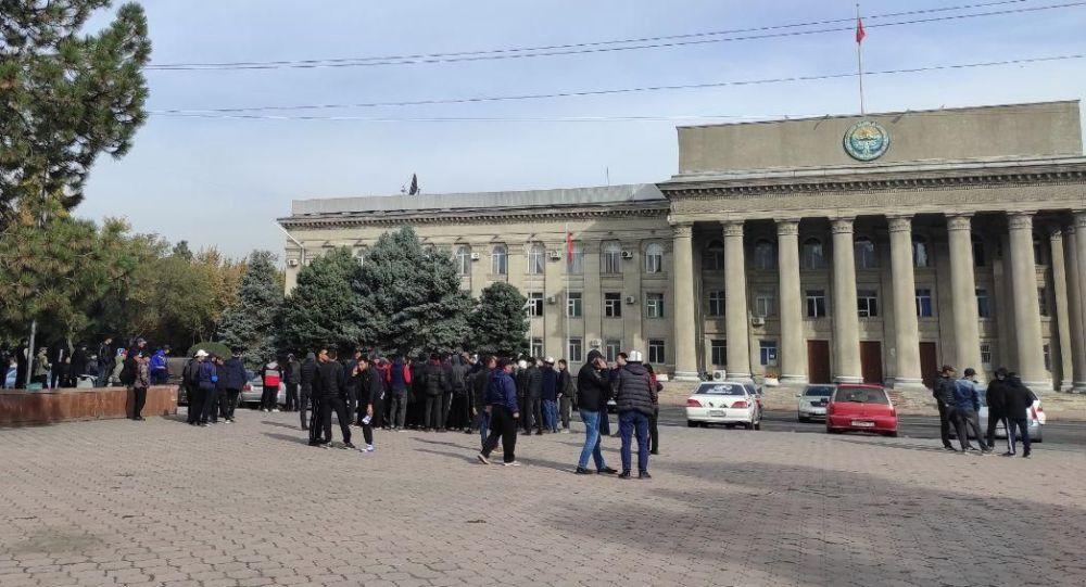 Люди собравшиеся на старой площади возле здания правительства в Бишкеке
