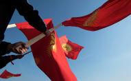 Люди с флагами КР на площади Ала-Тоо в Бишкеке. Архивное фото