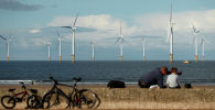 Люди сидят на пляже в Редкаре на фоне ветряных мельниц