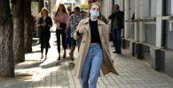 Девушка в медицинской маске на одной из улиц города