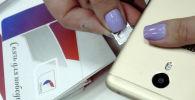 Девушка меняет сим карту на телефоне. Архивное фото