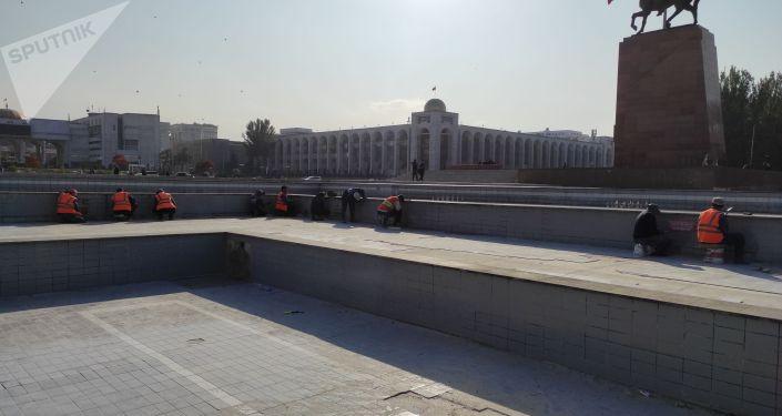 Сотрудники Тазалык во время уборки на площади Ала-Тоо в Бишкеке после прошедших накануне беспорядков