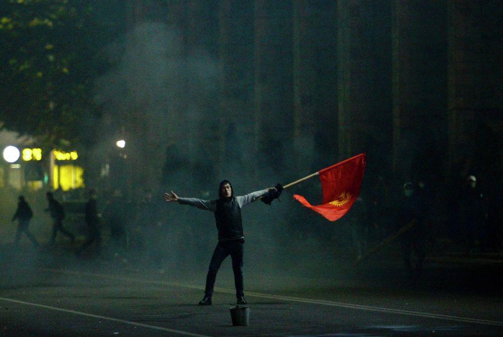 Протестующий машет флагом Кыргызстана во время столкновений с правоохранительными органами.