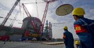 Рабочие наблюдают, как поднимается купол, чтобы соответствовать конструкции защитной оболочки для реактора № 1 на строительной площадке Чанцзянской атомной электростанции в Чанцзяне в провинции Хайнань на юге Китая. 28 декабря 2011 года