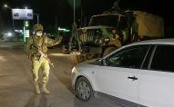 Военнослужащий останавливает машину во время комендантского часа в Бишкеке. Архивное фото