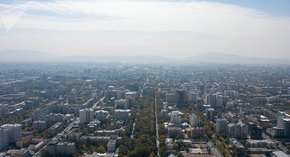 Вид на проспект Эркиндик в Бишкеке с высоты окутанный смогом