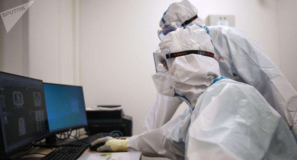 Компьютердик томографияны карап жаткан медициналык кызматкерлер
