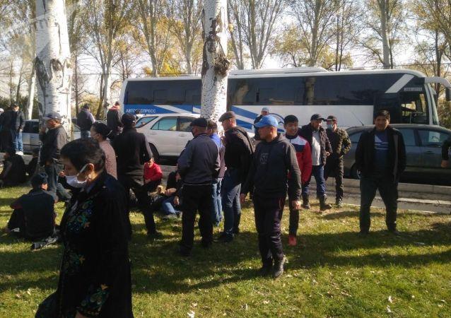 Митингующие за отставку президента Сооронбая Жээнбекова выходят из автобусов возле гостиницы Иссык-Куль в Бишкеке. 15 октября 2020 года