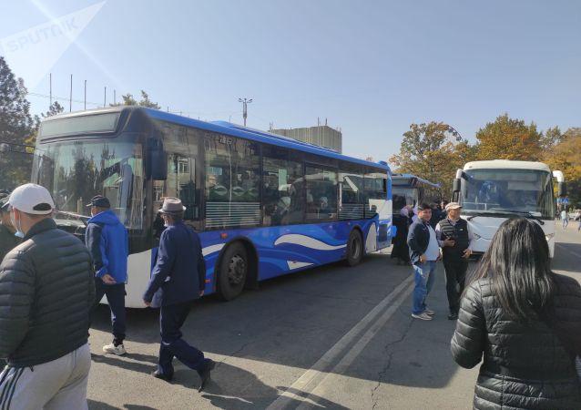 Митингующие за отставку президента Сооронбая Жээнбекова возле автобусов у дома правительства в Бишкеке . 15 октября 2020 года