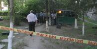 Сотрудники милиции возле жертвы убийства у центра консультативных услуг и спортивной медицины на проспекте Манаса в Бишкеке