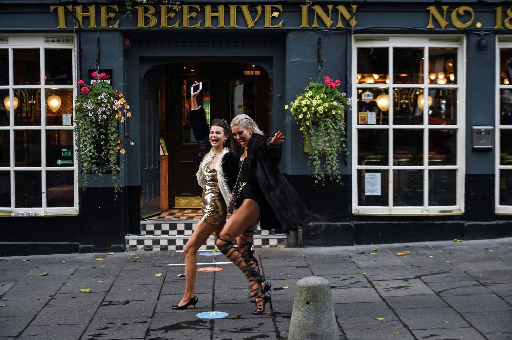 Девушки позируют возле гостиницы The Beehive Inn,  в Эдинбурге, 9 октября 2020 года. - В Шотландии закрывают на две недели пабы в центральной части страны, включая главные города Глазго и Эдинбург, поскольку правительство пытается сдержать рост случаев коронавируса.