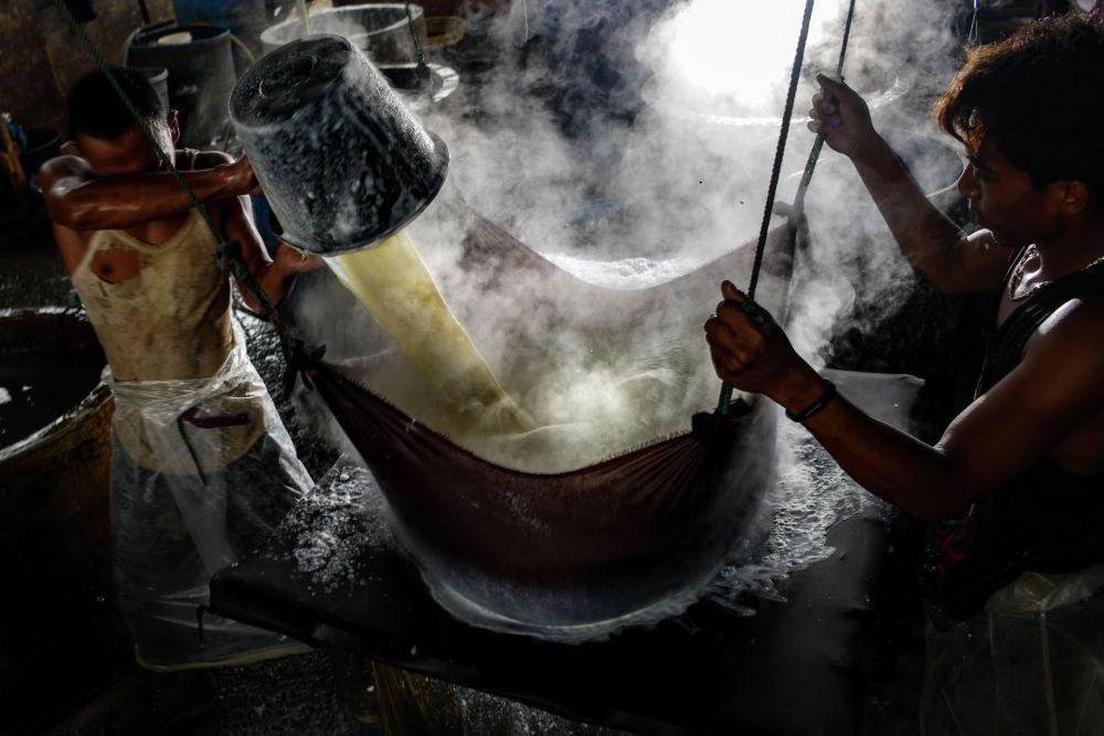Рабочие делают тофу из соевых бобов на предприятии в Банда-Ачех 12 октября 2020 года
