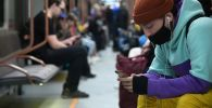 Пассажир метро со смартфоном в руках. Архивное фото