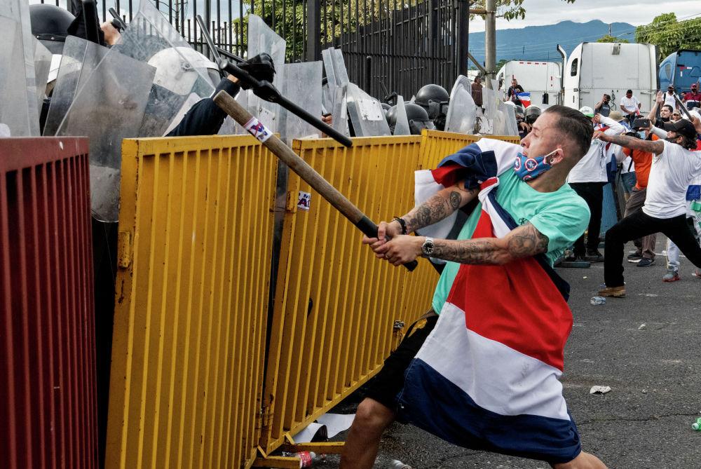 Протестующий с флагом Коста-Рики и металлической трубой противостоит полиции во время акции протеста против предложения правительства увеличить налоги с целью достижения кредитного соглашения с Международным валютным фондом (МВФ) у президентского дома в Сан-Хосе. 12 октября 2020 года