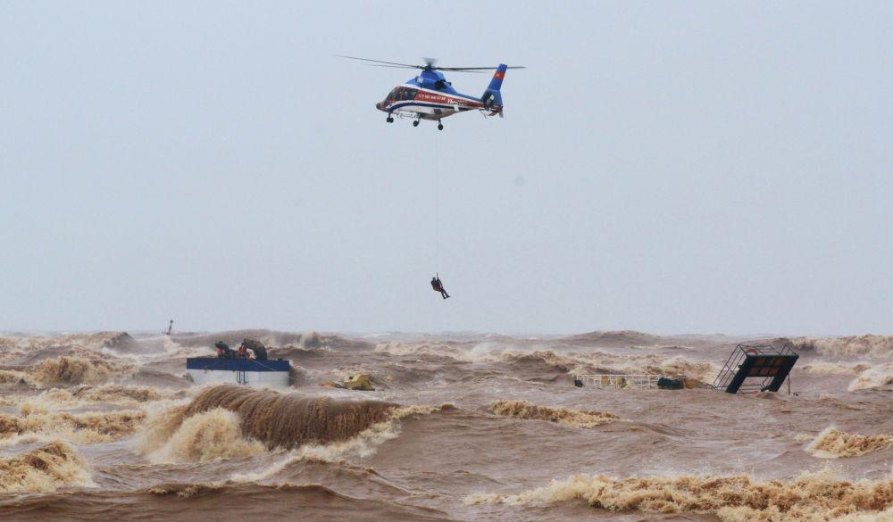 Военный вертолет спасает моряков затонувшего корабля в порту Куа Вьет в провинции Куангри, Вьетнам, 11 октября 2020 года.