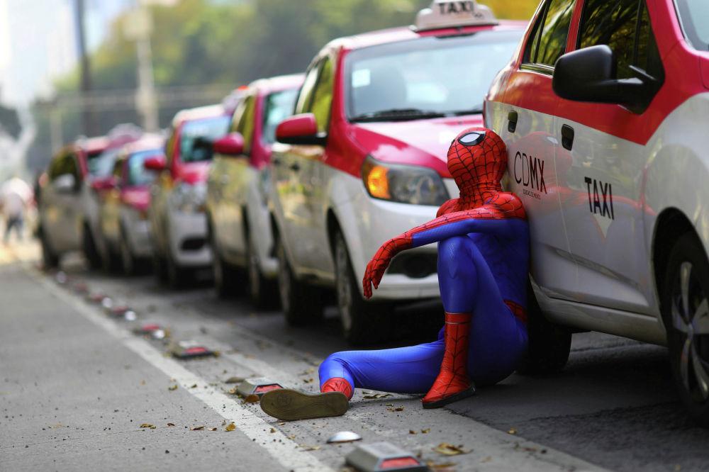 Человек в костюме Человека-паука сидит рядом с такси, когда таксисты проводят акцию протеста против приложений для вызова такси, таких как Uber, Cabify и Didi, у памятника Анхелю де ла Индепенденсия в Мехико, Мексика, 12 октября 2020 г.