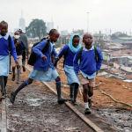 Школьники гуляют по железнодорожной линии Кения-Уганда во время частичного открытия школ после того, как правительство отменило планы отмены учебного года из-за пандемии коронавирусной болезни (COVID-19) в трущобах Кибера в Найроби, Кения, 12 октября 2020 года