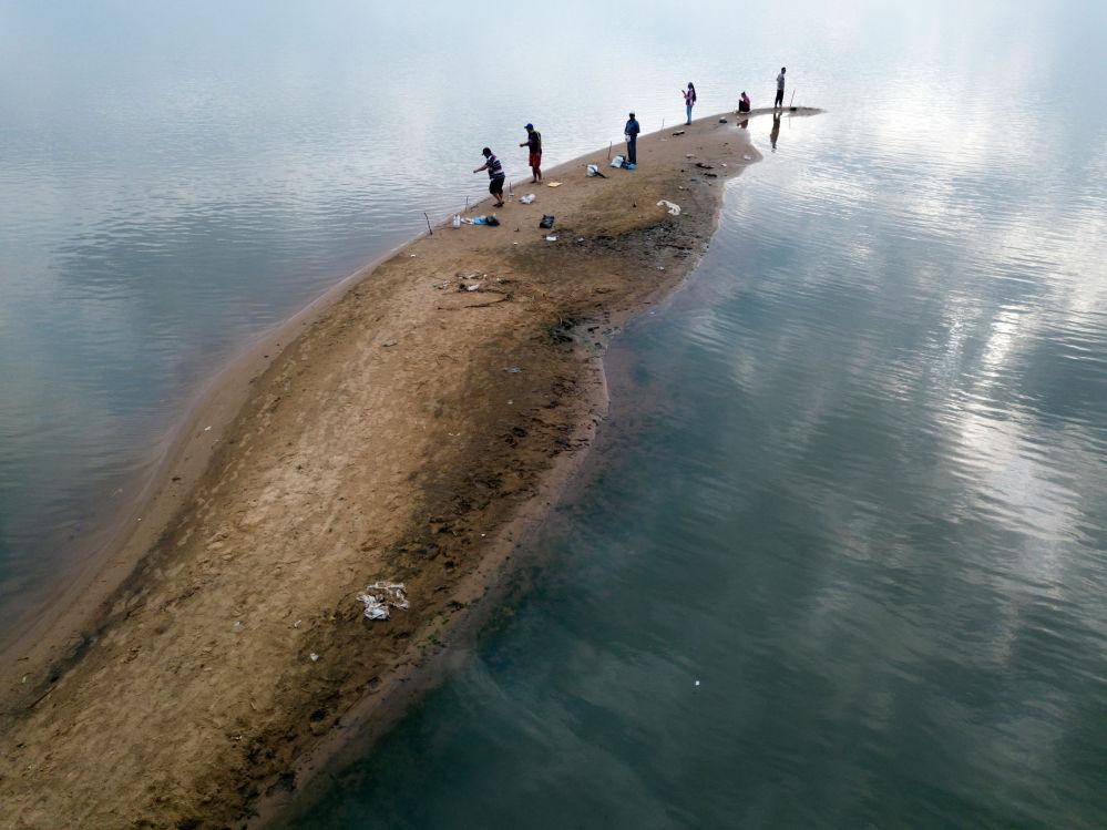 Мужчины ловят рыбу с песчаного отмели на реке Парагвай, пользуясь историческим падением уровня воды, в Сан-Антонио, на окраине Асунсьона, в четверг, 15 октября 2020 г.