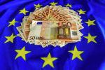 Банкноты евро на фоне флага Евросоюза. Иллюстративное фото