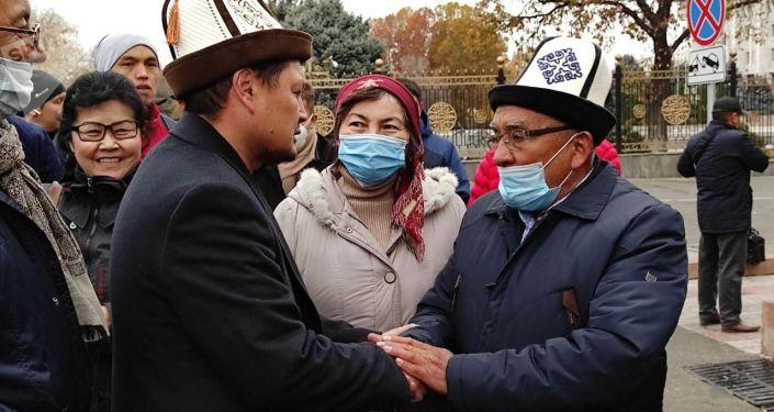 Глава Финансовой полиции Сыймык Жапыкеев на площади Ала-Тоо в Бишкеке во время поминальной молитвы погибшему 19-летнему Умутбеку Алтынбеку улуу. 23 октября 2020 года