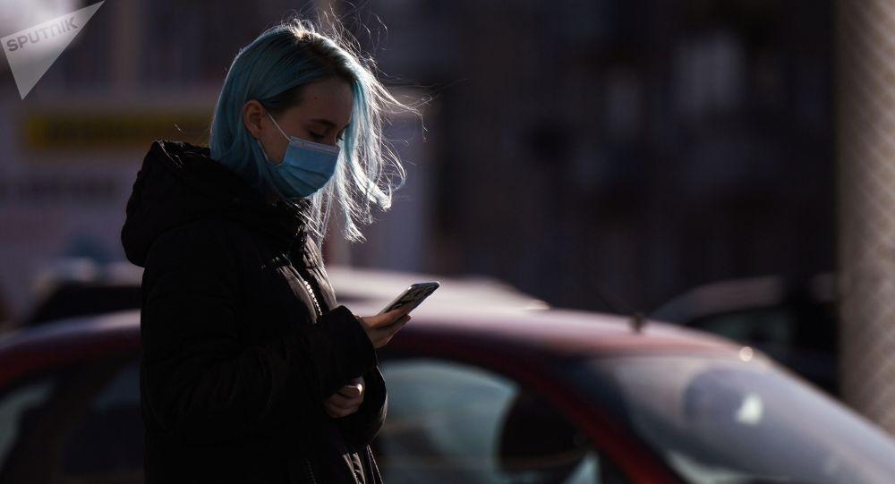 Девушка на улице со смартфоном в руках. Архивное фото