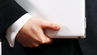 Ноутбук кармаган киши. Архивдик сүрөт