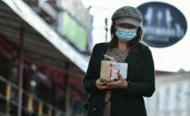 Девушка в защитной маске идет по улице. Архивное фото