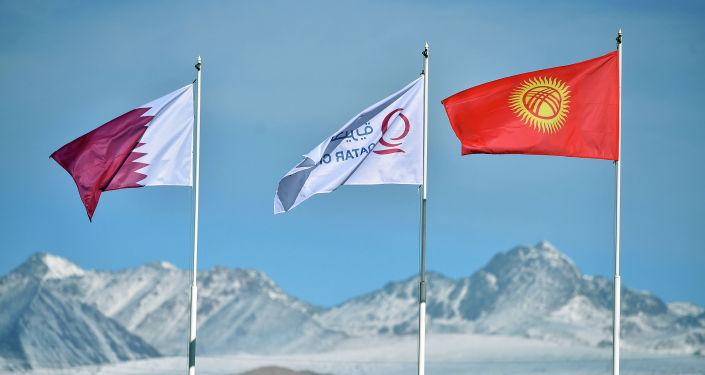 Флаги Кыргызстана и благотворительной организации Катар Чарити во время рабочей поездка и. о. Президента Садыра Жапарова в Кочкорский район Нарынской области. 25 октября 2020 года