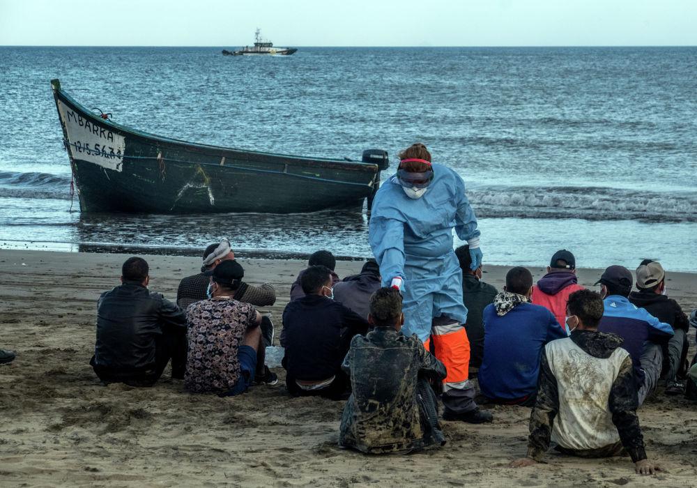 Мигрантам, прибывшим на Канарские острова из Марокко, измеряют температуру. 20 октября 2020 года