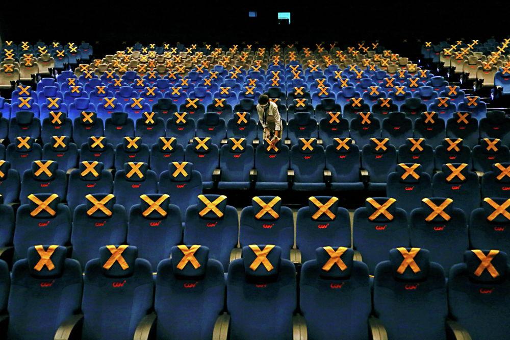 Сотрудник кинотеатра отметил места для социального дистанцирования из-за высокого уровня заражения на фоне пандемии COVID-19 в Джакарте