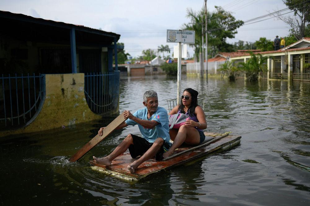 Жители венесуэльского города Маракай плывут на двери по затопленной улице.